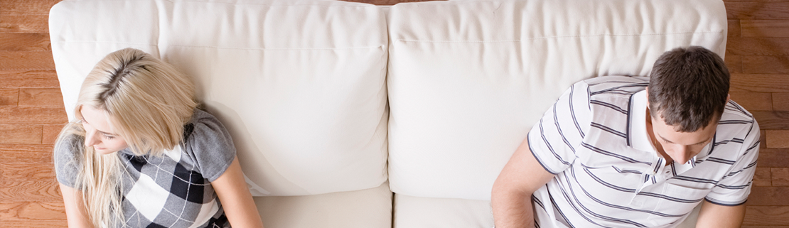 couple-sitting-on-either-side-of-white-couch-during-a-session-with-a-divorce-mediator