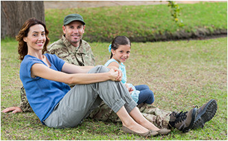 veteran family sitting outside on the grass